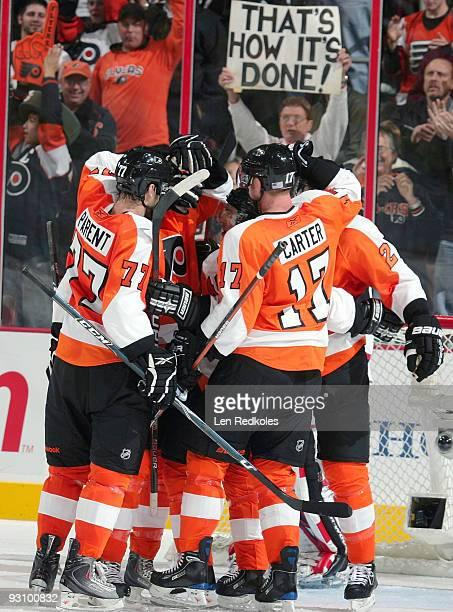 Ryan Parent, Jeff Carter, and James van Riemsdyk of the Philadelphia Flyers celebrate van Riemsdyk's third-period goal against the New Jersey Devils...