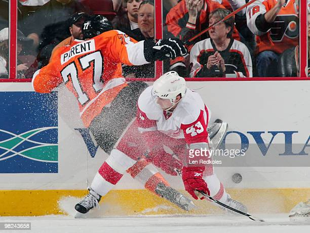 Ryan Parent of the Philadelphia Flyers is checked into the boards by Darren Helm of the Detroit Red Wings on April 4 2010 at the Wachovia Center in...