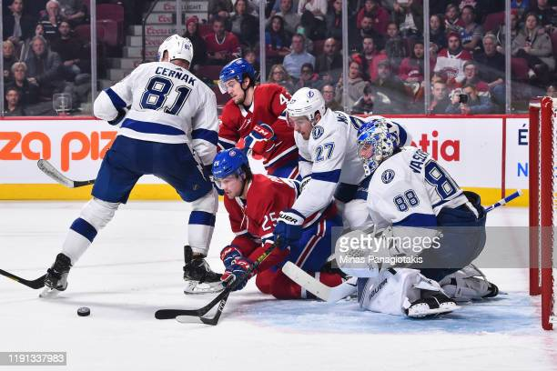 Ryan Poehling of the Montreal Canadiens and Ryan McDonagh of the Tampa Bay Lightning battle for the puck near goaltender Andrei Vasilevskiy during...