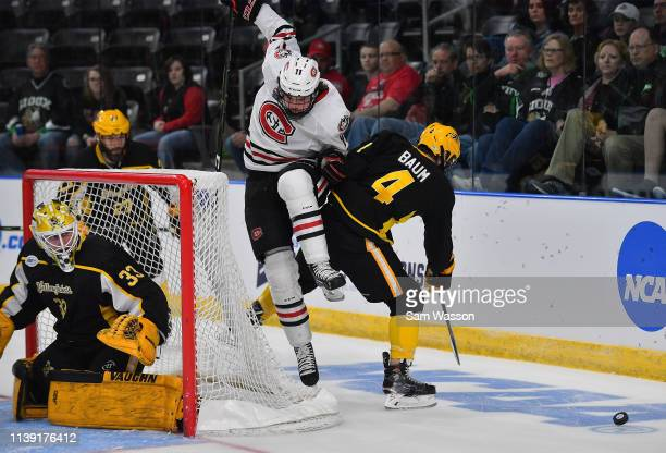 Ryan Poehling of the St Cloud State Huskies jumps in the air as Jeff Baum of the American International Yellow Jackets skates after the puck during...