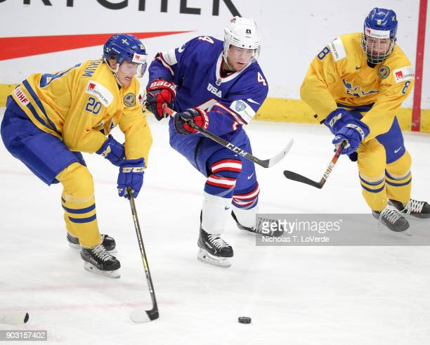 Ryan Poehling of United States passes the puck though the defensive pressure from Isac Lundeström and Rasmus Dahlin of Sweden during the first period...
