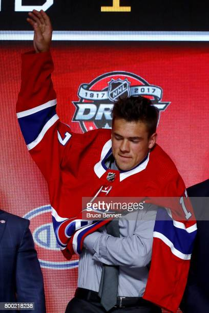 Ryan Poehling puts on the Montreal Canadiens jersey after being selected 25th overall during the 2017 NHL Draft at the United Center on June 23 2017...