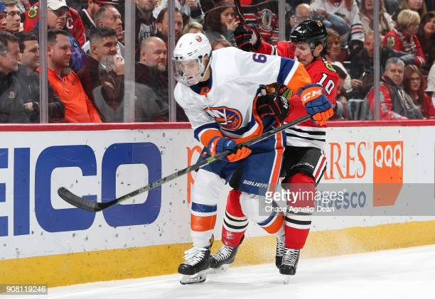 Ryan Pulock of the New York Islanders and Patrick Sharp of the Chicago Blackhawks get physical in the second period at the United Center on January...