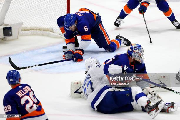 Ryan Pulock of the New York Islanders blocks a shot by Ryan McDonagh of the Tampa Bay Lightning during the third period in Game Four of the Stanley...