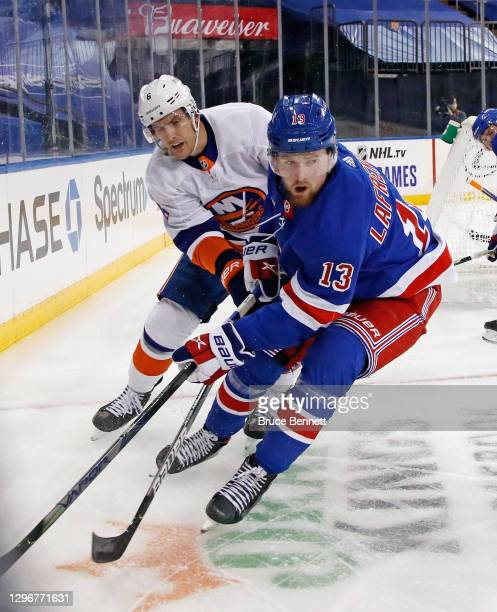 Ryan Pulock of the New York Islanders checks Alexis Lafreniere of the New York Rangers during the second period at Madison Square Garden on January...