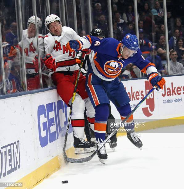 Ryan Pulock of the New York Islanders checks Justin Williams of the Carolina Hurricanes into the boards during the first period at NYCB Live's Nassau...