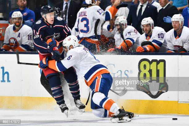 Ryan Pulock of the New York Islanders checks Matt Calvert of the Columbus Blue Jackets off the puck during the first period of a game on December 14...