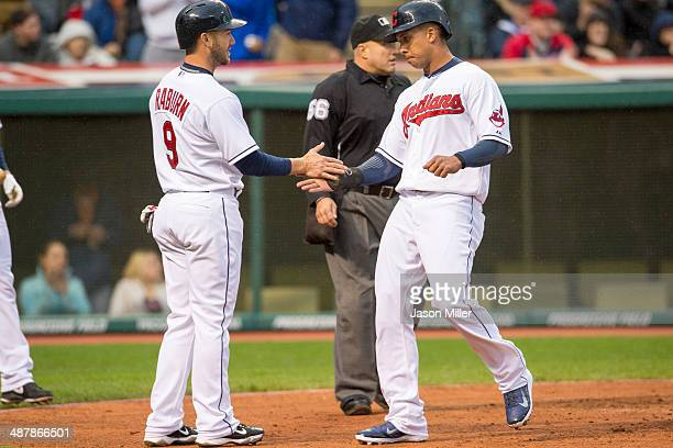 Ryan Raburn and Michael Brantley of the Cleveland Indians celebrate after scoring on a double by Yan Gomes during the first inning against the...