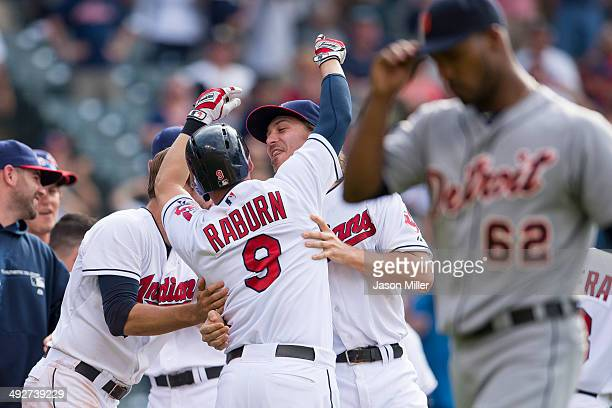 Ryan Raburn of the Cleveland Indians celebrates with teammates after the winning run was given up on a balk by Al Alburquerque of the Detroit Tigers...