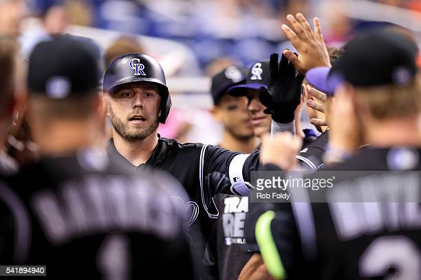 Ryan Raburn of the Colorado Rockies celebrates with teammates after hitting a solo home run during the second inning of the game against the Miami...