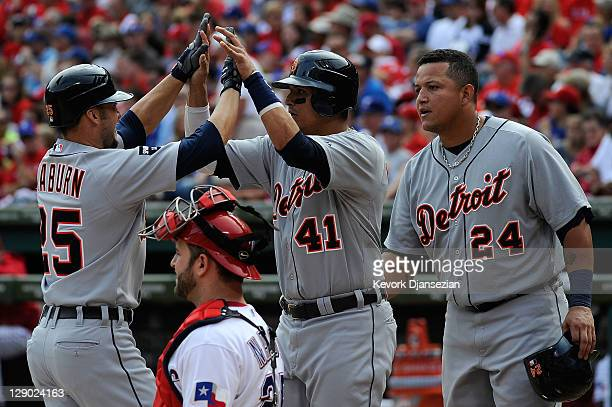 Ryan Raburn of the Detroit Tigers celebrates his three-run home run with Victor Martinez and Miguel Cabrera in the third inning of Game Two of the...