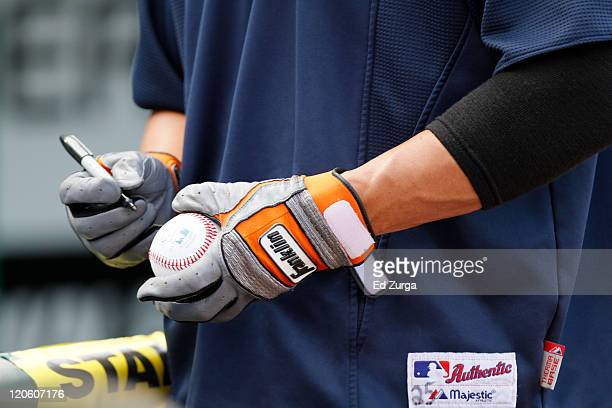 Ryan Raburn of the Detroit Tigers signs autographs with his Franklin batting gloves on during a game against the Kansas City Royals at Kauffman...