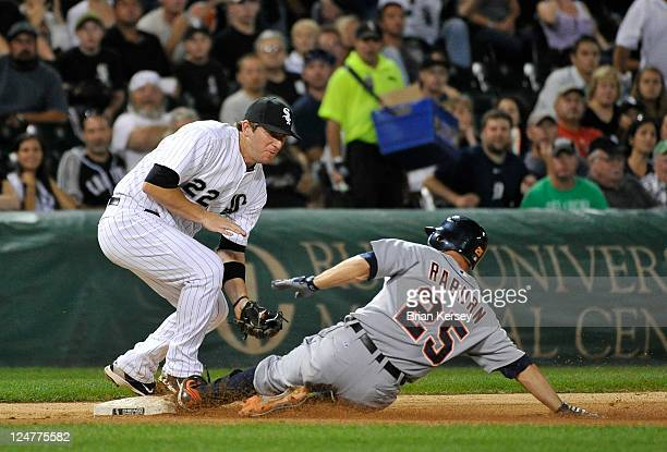 Ryan Rayburn of the Detroit Tigers slides safely into third base as third baseman Brent Morel of the Chicago White Sox catches the throw from left...