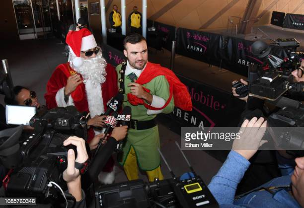 Ryan Reaves of the Golden Knights dressed as Santa Claus and William Carrier of the Golden Knights dressed as an elf are interviewed after giving out...