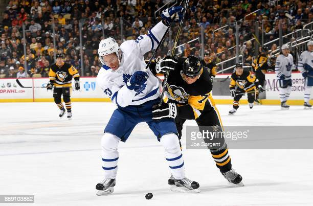 Ryan Reaves of the Pittsburgh Penguins and Dominic Moore of the Toronto Maple Leafs battle for the puck at PPG Paints Arena on December 9 2017 in...