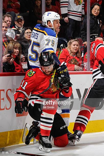 Ryan Reaves of the St. Louis Blues and Andrew Desjardins of the Chicago Blackhawks get physical by the boards in the first period of the NHL game at...
