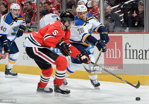 Ryan Reaves of the St Louis Blues and David Rundblad of the Chicago Blackhawks chase the puck as Maxim Lapierre follows behind during the NHL game at...