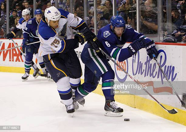 Ryan Reaves of the St Louis Blues fights for the puck against Yannick Weber of the Vancouver Canucks during the first period of their NHL game at...