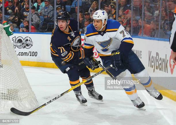 Ryan Reaves of the St Louis Blues pursues the puck while being defended by Evan Rodrigues of the Buffalo Sabres during an NHL game at the KeyBank...