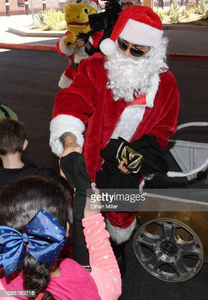 Ryan Reaves of the Vegas Golden Knights dressed as Santa Claus gives out gifts to kids before the team's game against the Montreal Canadiens at...