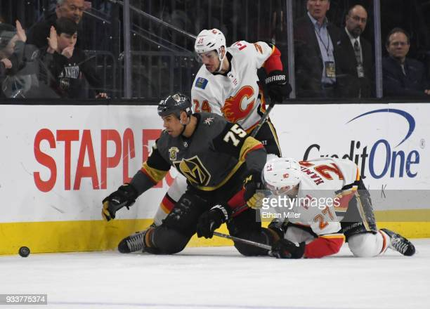 Ryan Reaves of the Vegas Golden Knights goes after a loose puck against Travis Hamonic and Dougie Hamilton of the Calgary Flames in the third period...