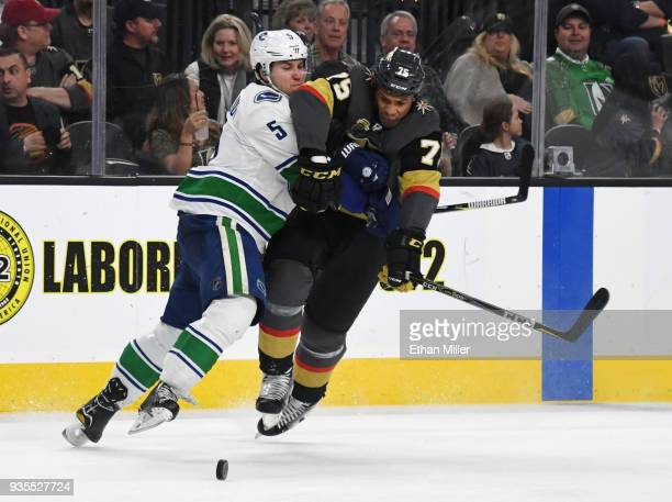 Ryan Reaves of the Vegas Golden Knights tries to get by Derrick Pouliot of the Vancouver Canucks in the second period of their game at TMobile Arena...