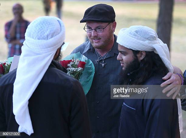 Ryan Reyes speaks with Nizaam Ali and Rahemaan Ali who came to pay their respects during a memorial service at the Santa Fe Dam Recreation Area for...