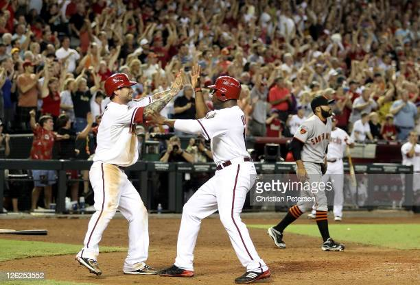 Ryan Roberts and Justin Upton of the Arizona Diamondbacks celebrate after scoring against the San Francisco Giants during the eighth inning of the...
