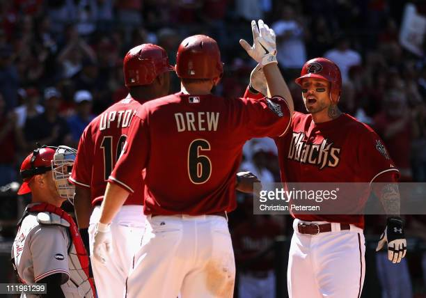 Ryan Roberts of the Arizona Diamondbacks highfives teammates Justin Upton and Stephen Drew after Roberts hit a threerun home run against the...