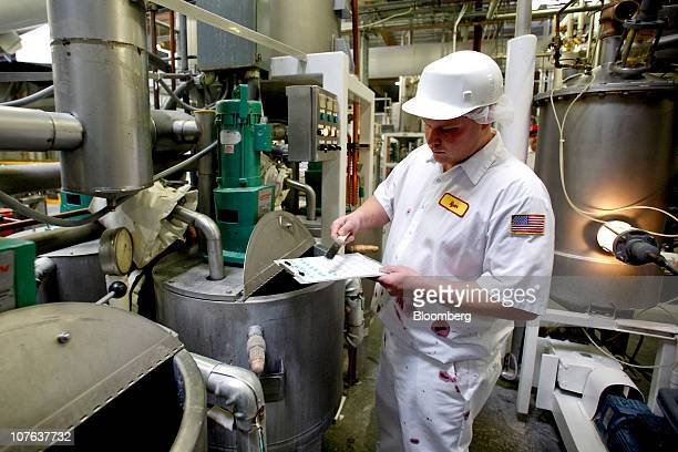 Ryan Rowland a sixth generation member of the family that owns Jelly Belly Candy Co takes a sample from a kettle of candy to check for color...