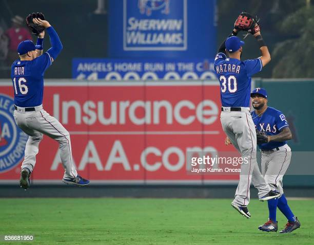 Ryan Rua Delino DeShields and Nomar Mazara of the Texas Rangers celebrate in the outfield after the final out of the ninth inning of the game against...