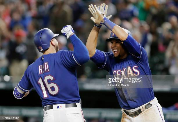 Ryan Rua of the Texas Rangers is congratulated by Carlos Gomez after hitting a grand slam during the eighth inning of a baseball game against the...