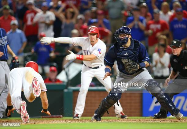 Ryan Rua of the Texas Rangers motions to Jared Hoying where to slide against Jesus Sucre of the Tampa Bay Rays at Globe Life Park in Arlington on May...