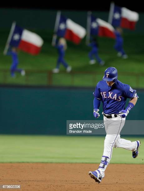 Ryan Rua of the Texas Rangers rounds the bases after hitting a grand slam during the eighth inning of a baseball game against the Minnesota Twins at...