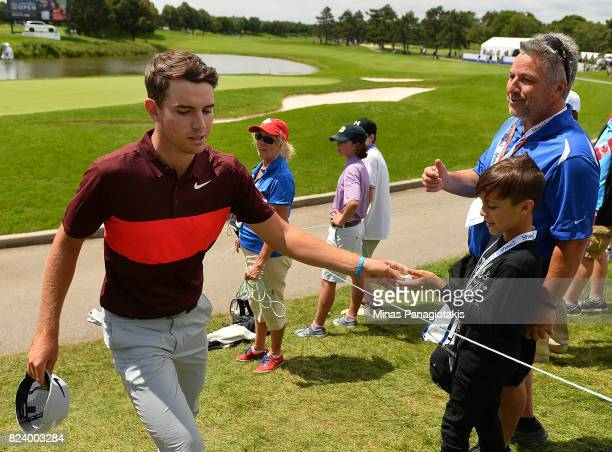 Ryan Ruffels of Australia hands a ball to a fan on the 18th hole during the second round of the RBC Canadian Open at Glen Abbey Golf Club on July 28...