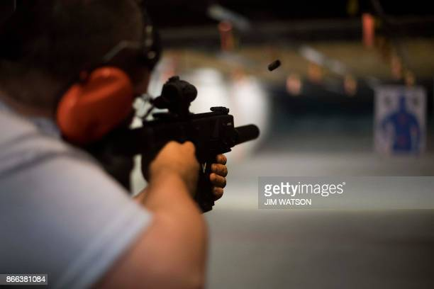 TOPSHOT Ryan Salmon fires an assault rifle at the Lynchburg Arms Indoor Shooting Range in Lynchburg Virginia on October 20 2017 Virginia residents go...