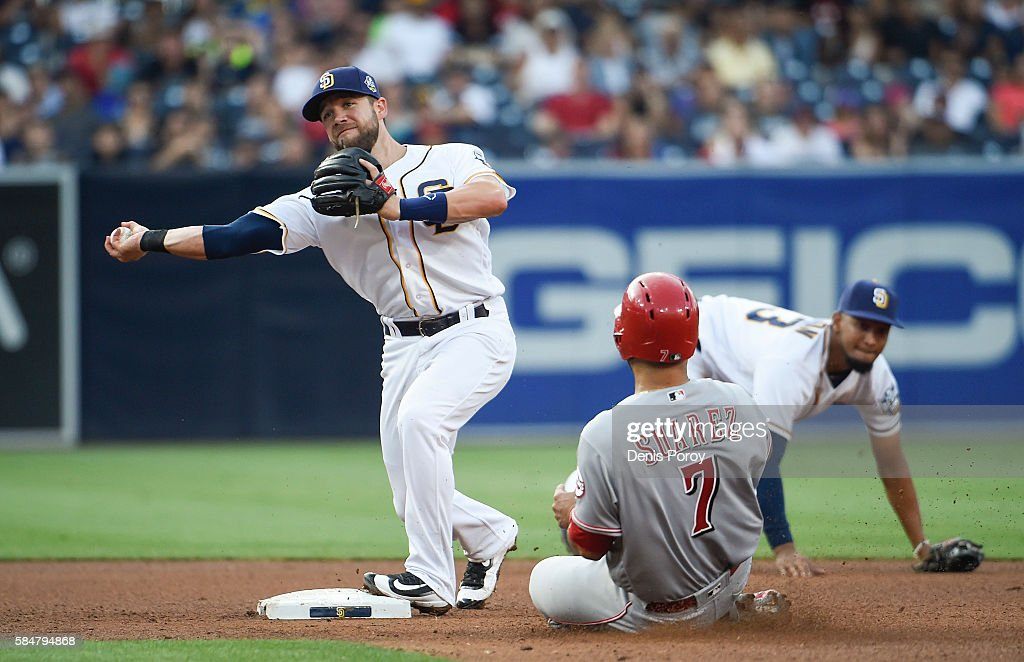 Ryan Schimpf #11 of the San Diego Padres throws over Eugenio Suarez #7 of the Cincinnati Reds as he turns a double play during the fifth inning of a baseball game at PETCO Park on July 30, 2016 in San Diego, California. Jose Rondon #13 of the San Diego Padres, right, made a diving stop on a ball hit by Tucker Barnhart #16 of the Cincinnati Reds to start the play.