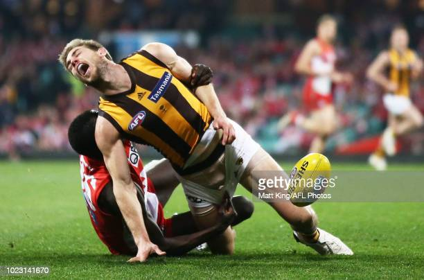 Ryan Schoenmakers of the Hawks is tackled by Aliir Aliir of the Swans during the round 23 AFL match between the Sydney Swans and the Hawthorn Hawks...