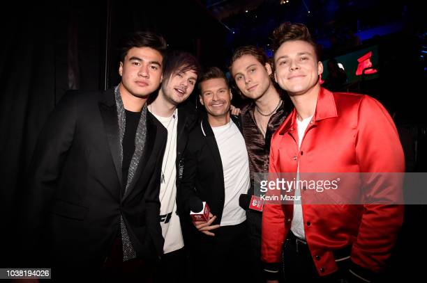 Ryan Seacrest poses with Calum Hood Michael Clifford Ashton Irwin and Luke Hemmings of 5 Seconds of Summer during the 2018 iHeartRadio Music Festival...