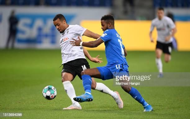 Ryan Sessegnon of TSG 1899 Hoffenheim battles for possession with Alassane Plea of Borussia Moenchengladbach during the Bundesliga match between TSG...