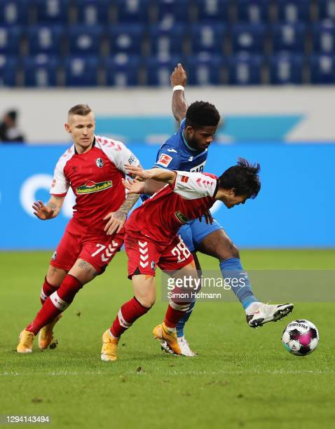 Ryan Sessegnon of TSG 1899 Hoffenheim is challenged by Kwon Chang-Hoon and Jonathan Schmid of SC Freiburg during the Bundesliga match between TSG...
