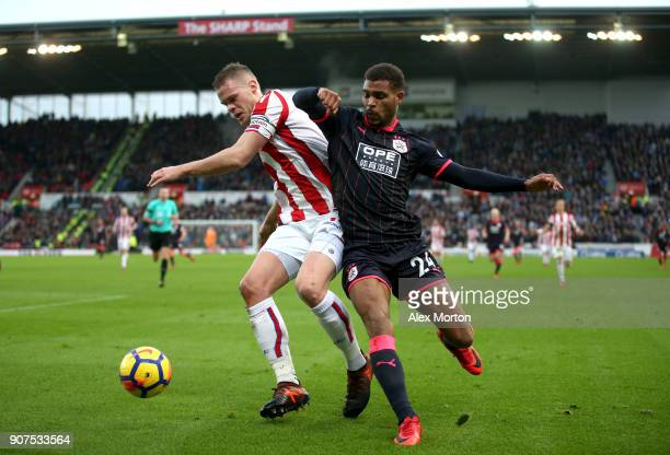 Ryan Shawcross of Stoke City is challenged by Steve Mounie of Huddersfield Town during the Premier League match between Stoke City and Huddersfield...