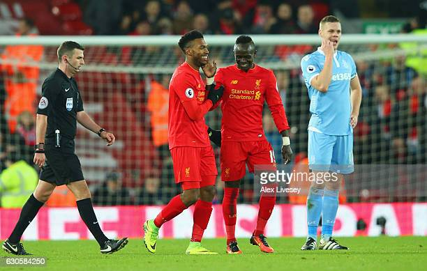 Ryan Shawcross of Stoke City looks dejected as Daniel Sturridge of Liverpool celebrates with team mates Sadio Mane as he scores their fourth goal...