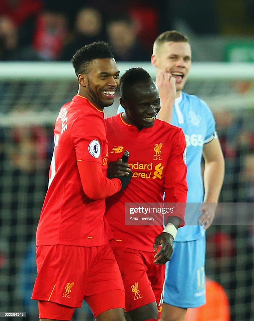 Ryan Shawcross of Stoke City (R) looks dejected as Daniel Sturridge of Liverpool (L) celebrates with team mates Sadio Mane as he scores their fourth goal during the Premier League match between Liverpool and Stoke City at Anfield on December 27, 2016 in Liverpool, England.