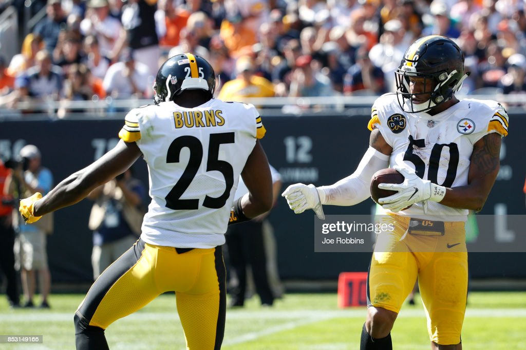 Ryan Shazier #50 and Artie Burns #25 of the Pittsburgh Steelers celebrate after Shazier recovered a fumble in the third quarter against the Chicago Bears at Soldier Field on September 24, 2017 in Chicago, Illinois.