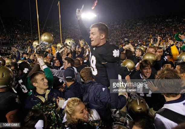 Ryan Sheehan of the Notre Dame Fighting Irish is lifted by students while celebrating a win over the Utah Utes at Notre Dame Stadium on November 13...