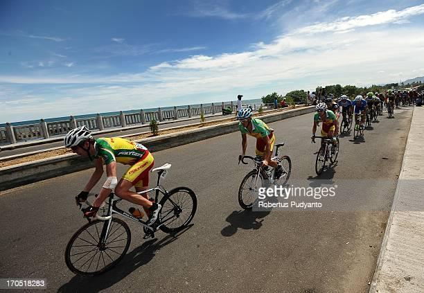 Ryan Sherlock and Sergey Kuzmin of Polygon Sweet Nice Cycling Team pass through the bridge alongside of Padang Beach in Stage 7 Tour de Singkarak...