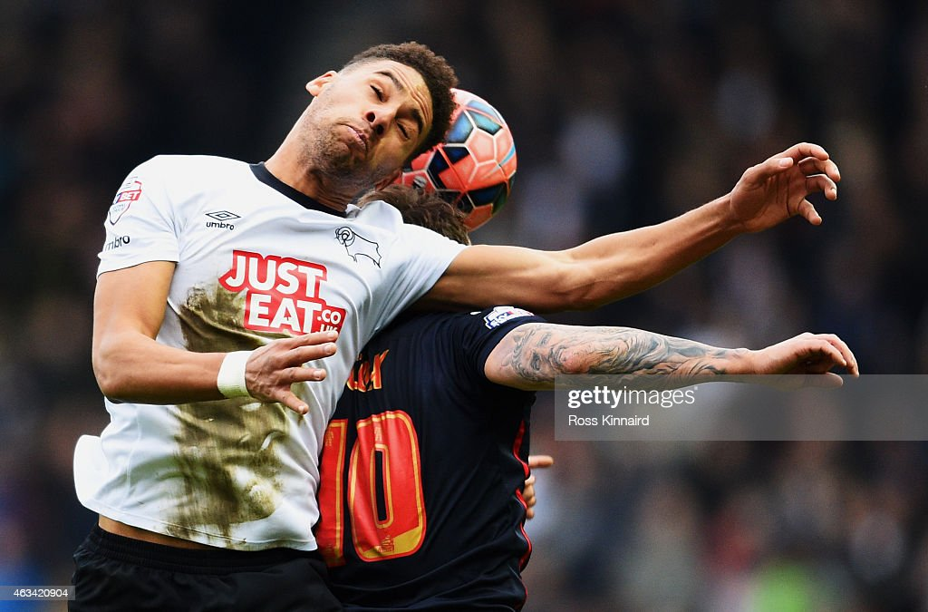 Ryan Shotton of Derby County jumps with Simon Cox of Reading during the FA Cup Fifth Round match between Derby County and Reading at iPro Stadium on February 14, 2015 in Derby, England.