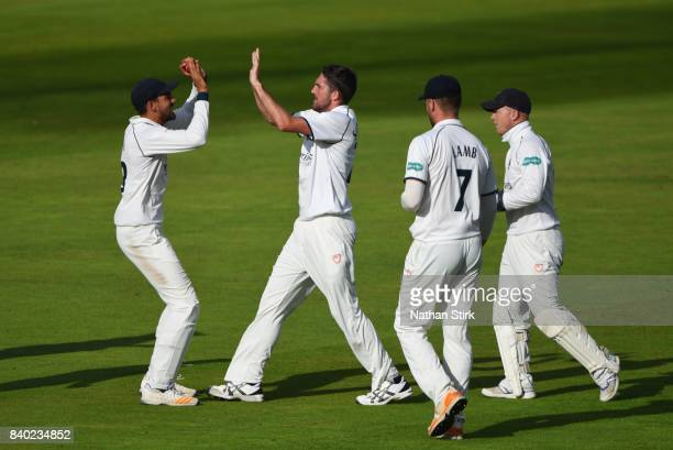 Ryan Sidebottom high fives Andrew Umeed of Warwickshire after he takes a wicket during the County Championship Division One match between Lancashire...