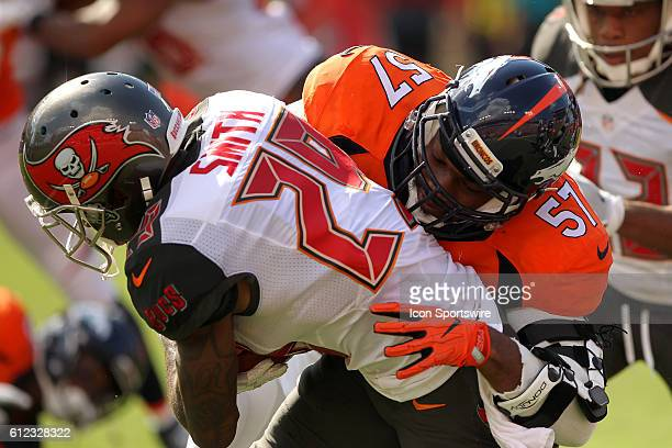 Ryan Smith of the Buccaneers is brought down by Dekoda Watson of the Broncos during the regular season game between the Denver Broncos and the Tampa...